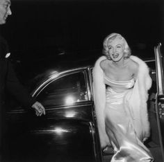 Marilyn Monroe steps out of her limo looking very regal in a white mink coat.