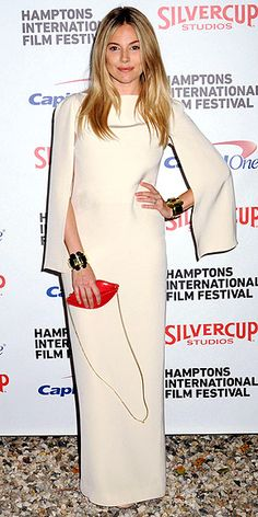 minimalist cream column with attached cape, plus dramatic golden cuffs and a cute lips clutch, at the Hamptons International Film Festival in Sag Harbor, N.Y.