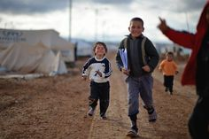 Moments of resilience, courage and even joy visible on the faces of Syrian #refugee children. Syrian refugee children play in the Zaatari refugee camp in #Jordan on Jan. 31, 2013. Jeff J. Mitchell / Getty Images