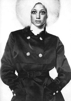 Marisa Berenson is wearing a black satin trenchcoat by John Cavanagh and a white fox beret by Otto Lucas.  Photo by David Bailey, 1968.