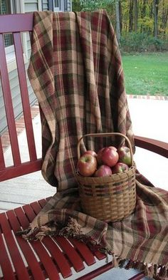 plaid thow on red rocking chair with apples in a basket