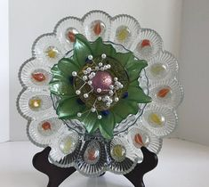 This Nature Land Candles offering is a Vintage Upcycled Glass Yard Art. This piece starts with a Vintage 12 large cut glass egg plate. Next we used a 7 clear blue glass saucer. We then used a green flower shaped bowl. For the center we used an amber glass hat with a purple knob and
