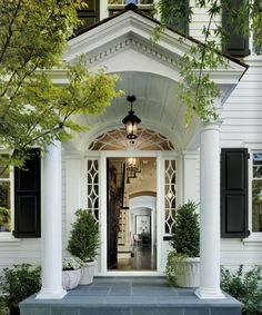 Beautiful entryway framed by black panelled shutters,  white clapboard exterior walls and potted topiaries.