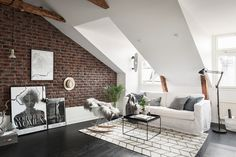 Living room in a Scandinavian attic apartment with exposed brick wall