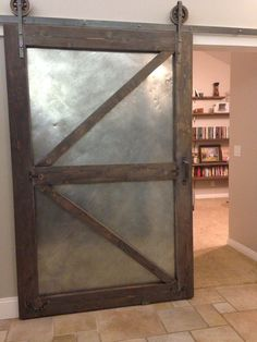 Industrial sliding barn door using aged sheet metal and distressed new lumbar. Chalkboard on back