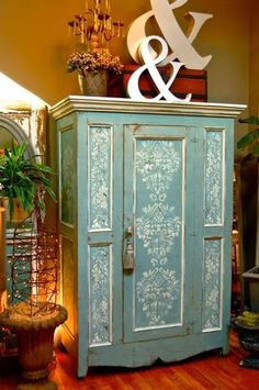 Debbie Hayes used Annie Sloan Chalk Paints (colors: Duck Egg Blue and Old White) and Royal Design Studio stencils to decorate this armoire. Center panel: Fabric Damask Stencil. Narrow side panels: Brocade Border Stencil.