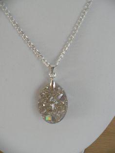 Ketting met hars hanger met zilverstof en zilver pailletten. De ketting is 45 cm lang. Hars sieraden. Decoratie voor de vrouw.