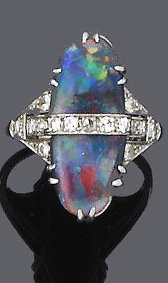 An art deco black opal and diamond ring, circa 1925 The oval-shaped cabochon black opal with central horizontal row of single-cut diamonds, to pierced graduated shoulders, diamonds approx. total, ring size P Opal Jewelry, Jewlery, Fine Jewelry, Art Deco Ring, Art Deco Jewelry, 1920s, Antique Jewelry, Vintage Jewelry, Black Opal