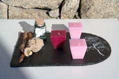 Passion Rose é uma decoração da ArteNatis constituída por:  - Uma base em ardósia preta, com acabamento de verniz mate, realçada com uma rosa pintada à mão com tinta branca;  - Três velas decorativas com tons de cor-de-rosa;  - Uma bola realizada à mão com corda fina de sisal;  - Uma mini garrafa de vidro com tampa em cortiça, preenchida com pedrinhas brancas.