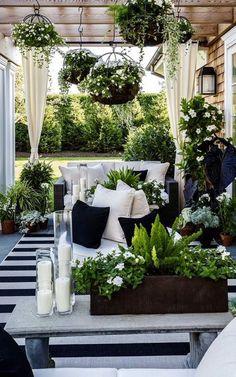 decoracion de terrazas, terraza en blanco y negro, sofá con cojines, mesa con candelas y flores, macetas colgantes #terrazaplantas