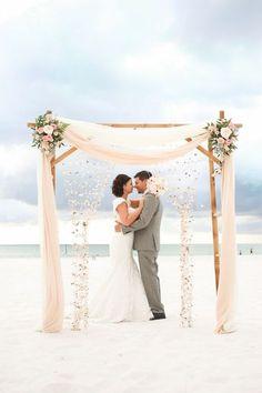 Decoración de ensueño para una boda en la playa. Una ceremonia en la playa de Clearwater Beach con un arco de bambú con flores y conchillas colgantes.