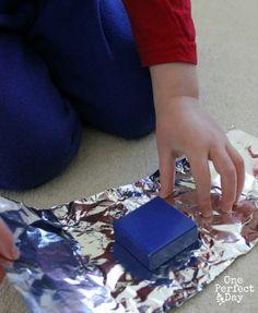 Une activité de motricité fine: Faire des paquets cadeaux avec du papier aluminium et des blocs de construction
