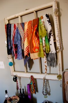 An old window frame with the glass removed can be turned into a scarf and necklace holder with some nails, hooks and florists wire.