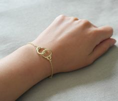 A gold handcuff suspended on gold plated chain