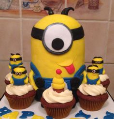 Despicable Me minion birthday cake surrounded by cupcakes