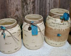 Add a touch of shabby chic to your home, bridal shower, wedding, or any other special occassion with these stunning hand painted jars. Each jar is hand painted, distressed, sprayed with matte protective sealant and finished with beautifully colored accents. Set of 3 jars. I upcyled these jars by painting them a beautiful turquoise and then sanded them to a trendy shabby chic look. I then finished off the shabby chic look with turquoise and ivory accents, paper flowers, burlap, natural jute…