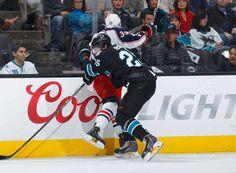San Jose Sharks forward Tye McGinn puts Michael Chaput of the Columbus Blue Jackets into the boards (Oct. 23, 2014).