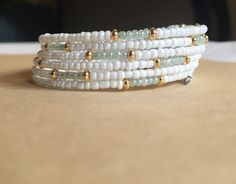 Memory wire bracelet, handcrafted with high quality glass seed beads. Ocean blue, gold, and white are the perfect accent for a spring or summer outfit! Very elegant styling to be dressed up or dressed down. This memory wire springs back in to place after you wrap the bracelet around your wrist. Choose between two sizes: petite or regular. Petite is for children, teenagers, or tiny adult wrists (like mine!).