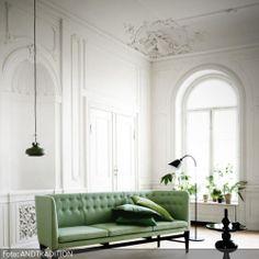 """Das Sofa """"Mayor AJ5"""" von andTradition ist der Hingucker in diesem hellen Altbau. Die Pendelleuchte """"Pendant SC8"""" und der Beistelltisch """"Shuffle Table"""" komplettieren den entspannten und klassischen Look des Wohnzimmers."""