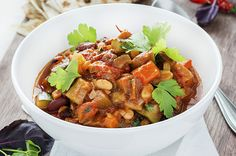 1 Tbsp. olive oil 2 medium red onions, peeled and chopped 2 cloves garlic, minced 4 large carrots, chopped 1/2 can (about 1 cup) red kidney beans, rinsed and drained 1/2 can (about 1 cup) white beans, rinsed and drained 2 red, yellow or orange peppers (capsicum), chopped 1 jar (about 2 cups) low-sodium organic tomato sauce, or make your own 1-2 tsp. chili powder Salt and pepper, to taste 2 Tbsp. dried or fresh basil 2 Tbsp. dried or fresh oregano 4 – 5 handfuls chopped kale