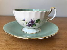 Aynsley Vintage Teacup and Saucer This is a beautiful teacup and saucer in the Oban shape and trimmed in gold. The centre and sides of the cup have lovely purple, blue and white violets with two toned green leaves. This set is white with a sage green border. This set is gorgeous and will