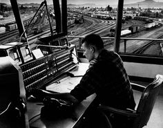 SP yardmaster at Eugene, Ore. - Here's a yardmaster at work, in a 1950s-style elevated tower overlooking the Southern Pacific yard in Eugene, Ore. The switchboard in front of him controls telephones, not turnouts. - Southern Pacific photo - from Classic Trains