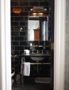 Brian Sawyer: Brian selected glossy black porcelain tiles and a marble washstand from Urban Archeology for the guest bath.