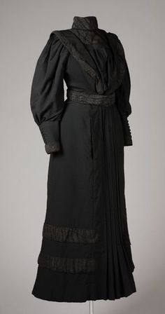 Two-piece mourning dress, Den Ouden Sisters, Netherlands, ca. 1900-10. Black wool with silk crepe. Long sleeves, wide cuffs. Decorative pleats at center front of skirt, pleated black silk crepe sash. Hook & eye closure.