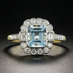 Recently made in London in classic Edwardian/early-Art Deco style, this cheerful and refreshing jewel is rendered in platinum over 18K yellow gold and highlights a beautiful sky blue emerald-cut aquamarine framed in bright-white round brilliant-cut diamonds with a pair of baguettes leading to diamond-set shoulders. Hallmarked inside ring shank. Currently ring size 6 1/2.