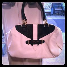 White and Black Olivia + Joy Satchel This purse features a beautiful black and white faux buckle design and two brilliant gold accent zippers. Center functional zipper opens to reveal a roomy interior, complete with a zippered pocket and three open-top pockets. Excellent condition. White is still pristine. Olivia + Joy Bags Satchels