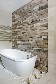 """A freestanding tub nestled into a bed of rocks against a natural stone backdrop recreates the relaxing sensation of soaking in your own private hot springs! Lightweight stone veneers make a perfect statement wall without breaking the bank! <br /><br />Natural Stone, St. Clair Ledgestone, <a href=""""http://stoneselex.com"""" target=""""_blank"""">Stone Selex</a>"""
