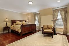 This bedroom is another example of dark wood bed frame matching hardwood flooring, with a large rug taking the expanse of the space.