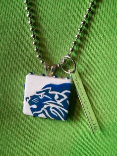 I take scrabble tiles and hand draw diff school mascots on them and then hand paint them, add colored rhinestones around the edges and seal with poly coat. I then engrave a tag with the name of the school. Add a bale to the back and a one of a kind school necklace.