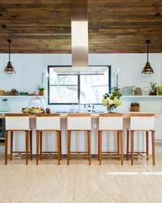 Bar stools and open shelving in Jenni Kayne's kitchen, lit by pendant lights