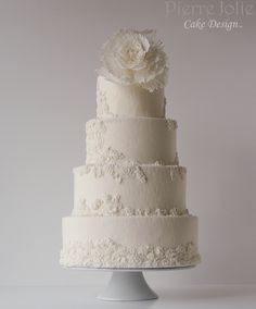 Classic White on White Wedding Cake adorned with sugar pearls and bas relief.