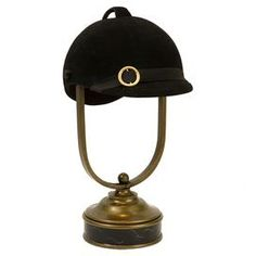"""Table lamp with a riding helmet-inspired shade.   Product: LampConstruction Material: Polyresin, iron, and fabricColor: Black and bronzeFeatures: Riding helmet shadeDimensions: 20"""" H x 15"""" W x 10.5"""" D"""