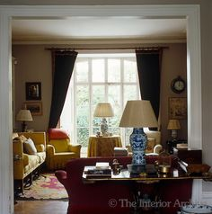 A wooden occasional table and a sofa partition the dining room from the adjoining sitting room in Lord Snowdon's London home