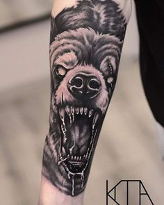 realistic black and grey bear tattoo on the forearm