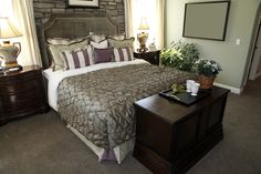 Different angle on bedroom pictured above, with stone brick wall and purple accents on the pillows andbed sheets.