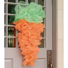 Curly wire mesh carrot door hanger hangs from attached wire.