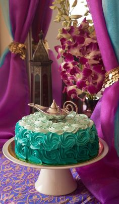 A Princess Jasmine-inspired teal cake topped with Aladdin's Lamp - perfect for an Arabian Nights theme party
