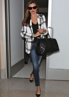 Miranda Ker con un shopping bag de Givenchy y blazer a cuadros en blanco y negro de Stella McCartney