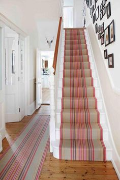 This style home with the grand entrance hallways and the stairs being one of the first visual points just cry out for a carpet stair runner just like this one.  I love the strips, and the colours are gorgeous especially against the pale walls and on the real stained wood floor.  I also love how the photo gallery runs up the stairs, all of this just makes you want to explore further. Although if it was me I would have maybe thrown in a few coloured frames too.