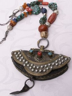 by Anne Marie of BeadArt Austria | Necklace; the focal pendant of this necklace is an antique money purse from Tibet (leather, coral, turquoise, brass and silver) that has been combined with antique gilded silver over lac bead from India, and vintage African amber bead, old Tibetan turquoise, sterling silver, contemporary coral beads, old carved lapis , carnelian bead and genuine butterscotch Baltic amber beads.