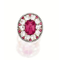 PINK SPINEL AND DIAMOND RING, IVY. Centring on a cushion-shaped pink spinel weighing 4.27 carats, surrounded by circular rose-cut diamonds, decorated by trilliant pink spinels, the diamonds together weighing approximately 2.65 carats, mounted in 18 karat pink and blackened gold, signed.
