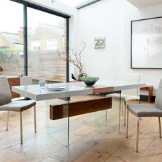The three differing materials used in our Treble range give it a unique look and lightness that almost, but not quite, makes its functionality secondary. This dining table extends centrally by simply pulling from either end. The table top is supported by lengths of toughened smoked glass and a walnut veneer cross bar. A distinct yet functional dining table that will easily be matched with some of our gloss or fabric dining chairs. The hidden panel under the middle part of the table…