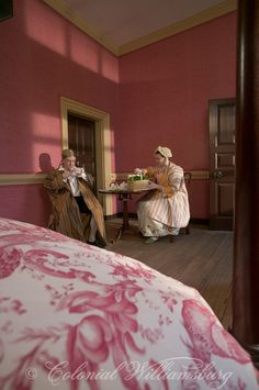 Breakfast shared on a small table in a bedchamber.