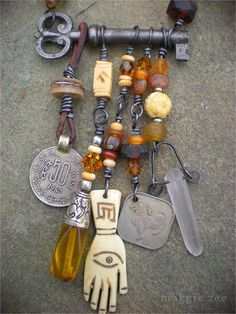 "Prosperity and Abundance Amulet Necklace. Coins to attract abundance and prosperity (based on the magical principle that ""like attracts like""); a Tibetan ""amber"" pendant (vintage, but probably a resin of some kind); a carved bone hand from Tibet (can be worn with the eye side facing out for protection or the open hand side to attract abundance); and a quartz crystal point to amplify all the good mojo.  By Maggiezees"