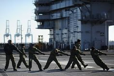 Sailors handle de-energized cables on the flight deck aboard the aircraft carrier USS George H.W. Bush (CVN 77) in preparation for a magnetic treatment (DEPERM) at Lambert Point Magnetic Treatment Facility.