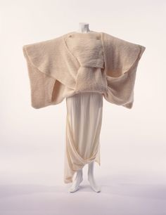comme des garcons 1983 デザイナー: 川久保玲 ブランド: コム・デ・ギャルソン レーベル: tricot COMME des GARÇONS(セーター)、COMME des GARÇONS(スカート) 素材・形状特徴: 生成のウール・ニットのセーター。ガーター編み、裾はゴム編み。生成のウール・ジャージーのスカート。 クレジット・ライン: 株式会社コム デ ギャルソン寄贈 川久保の初期を代表する一点。複雑に交差するセーターは、基本的に直線のパネルで構成されて、力強い量感を示している。たっぷりとしたゆとりは、左右に広げた袖は着物の袖を想わせる。スカートは、セーターのゆとりやたるみが生み出す不定型な形に呼応して、アシンメトリーにたわんでいる。 川久保は、1980年代はじめ、無彩色、ぶかぶか、アシンメトリー、意識的な穴や破れを施した、西欧の既存の美意識を覆す作品によってパリで賛否両論を巻き起こした。その後も、既成概念にとらわれないという一貫する姿勢を服に具現化していった。